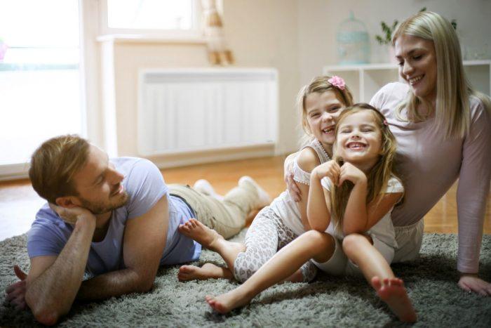 famille dans un salon avec un radiateur a inertie aterno en arrière plan